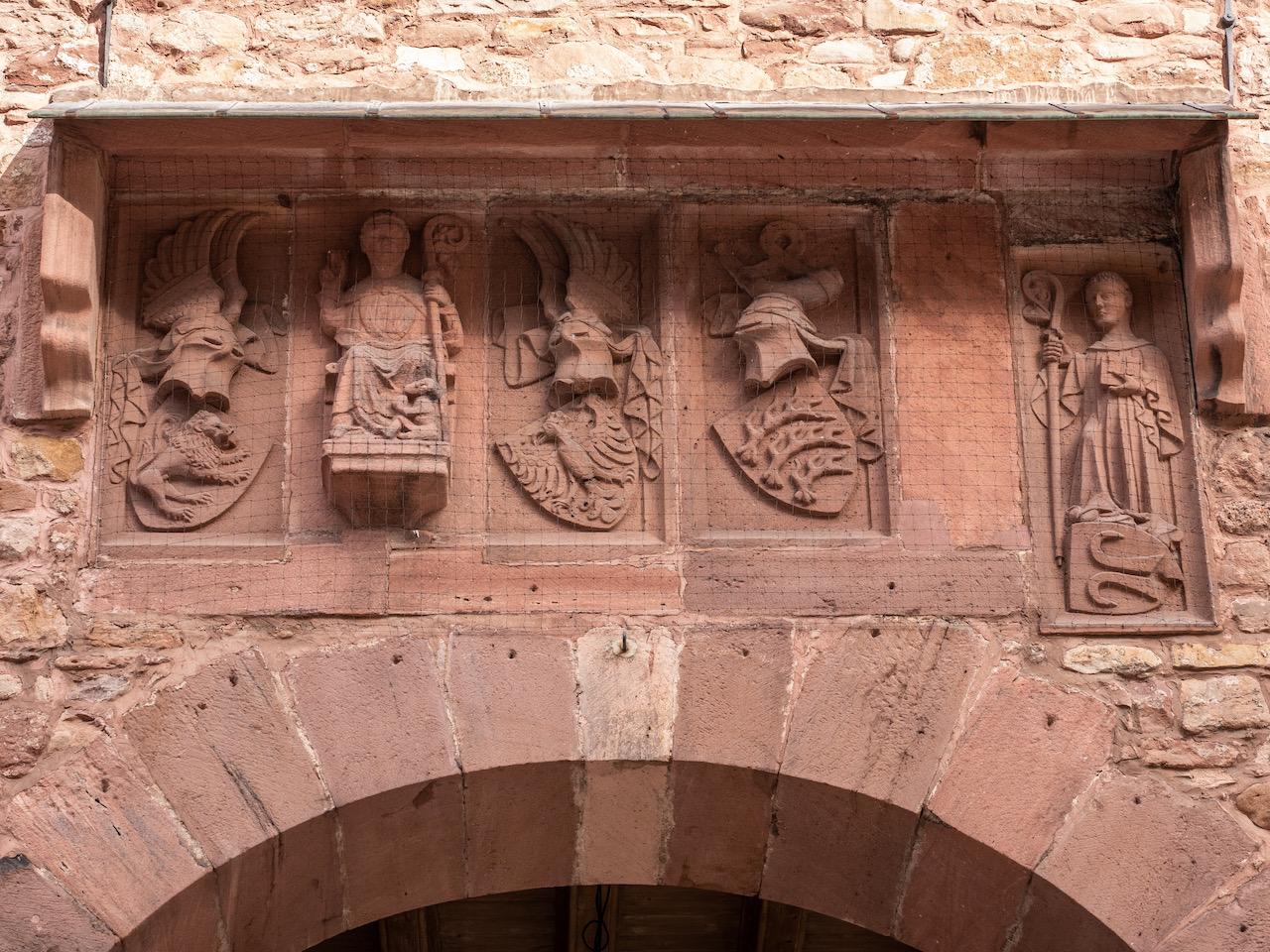 Wappenreihe mit Wappen einer Stifterfamilie, Wappen der Grafen von Württemberg, Relief des hl. Benedikt und Relief des Abts Heinrich Hack über dem Mittelbogen der Vorhalle (frühes 15. Jh.)