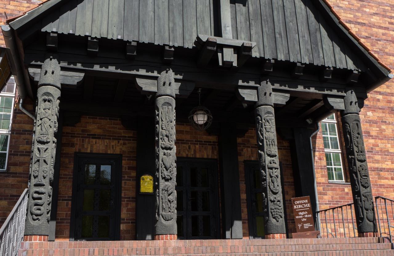 Vorhalle mit den vier Evangelisten gewidmeten Holzsäulen