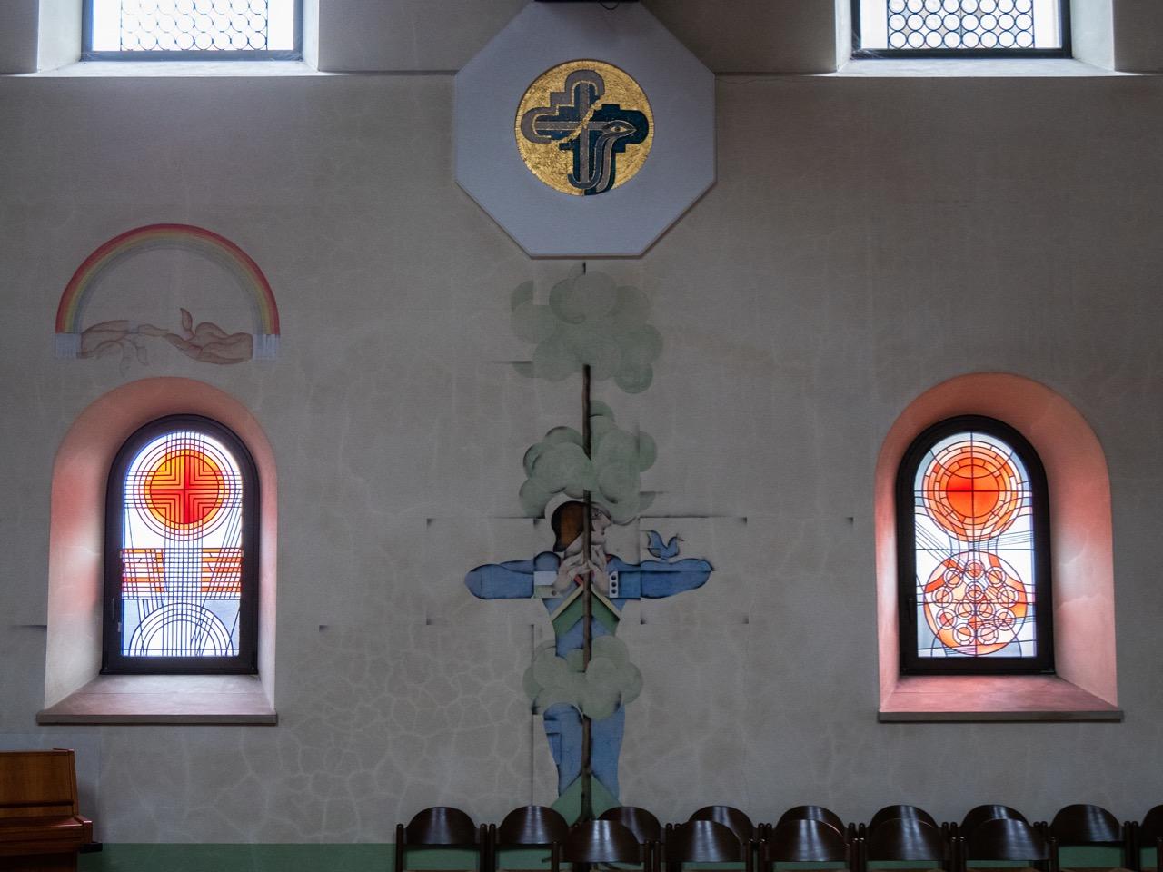 Südwand mit Buntglasfenstern von Gerhard Dreher, Fresko von Lude Döring und Auflageremblem von Ursula Stock