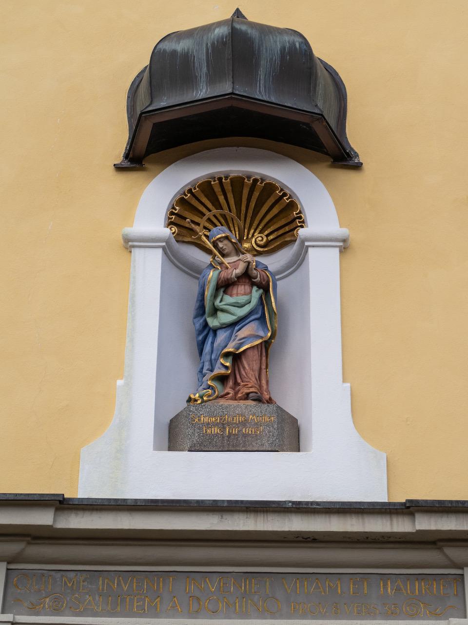 Portalfigur der Maria Dolorosa und Zitat aus Spr. 8,35: Wer mich findet, der findet das Leben und erlangt Wohlgefallen vom Herrn.