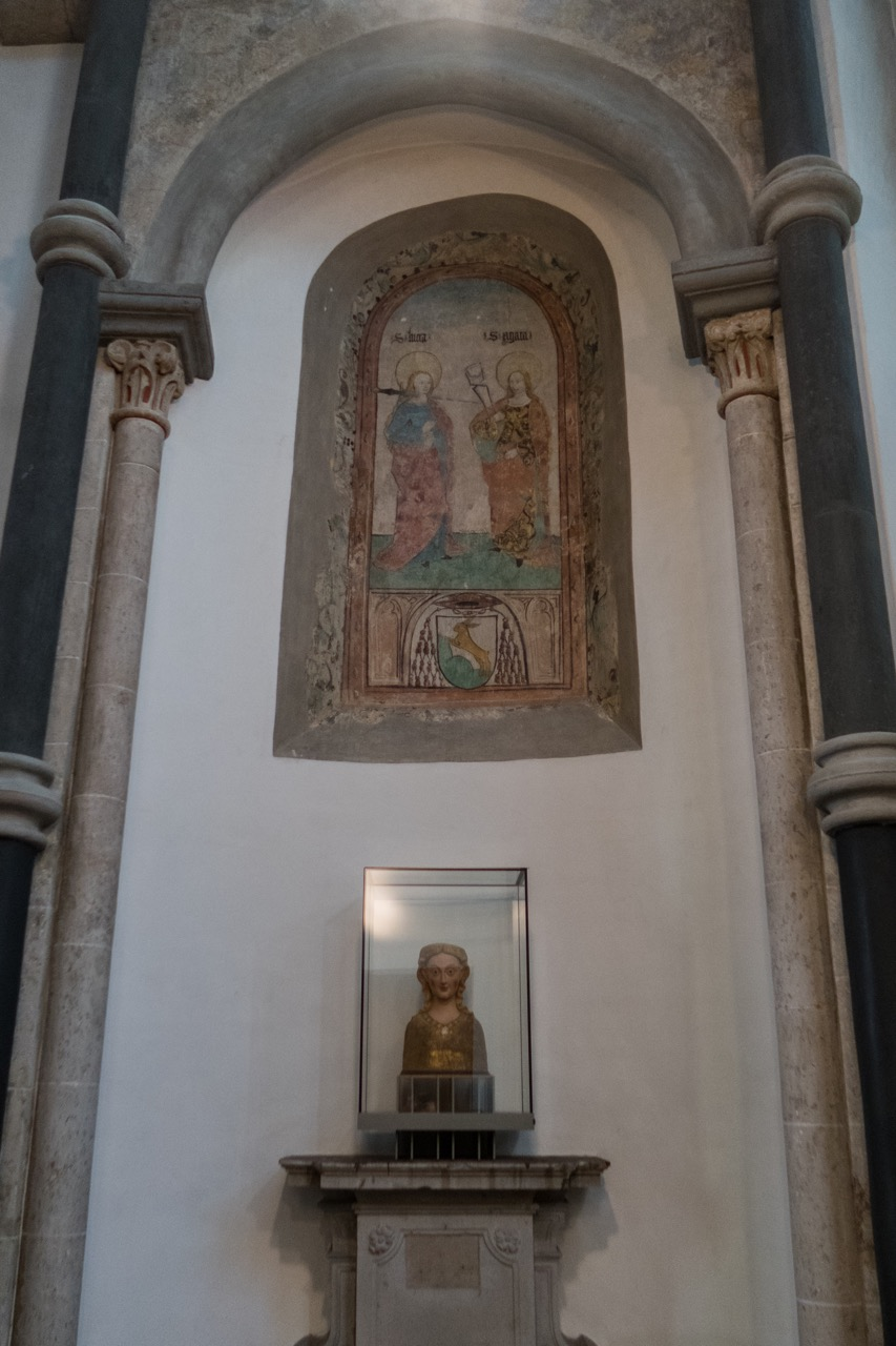 Fresko der Hl. Lucia und Agata in einem zugemauerten romanischen Fensterbogen