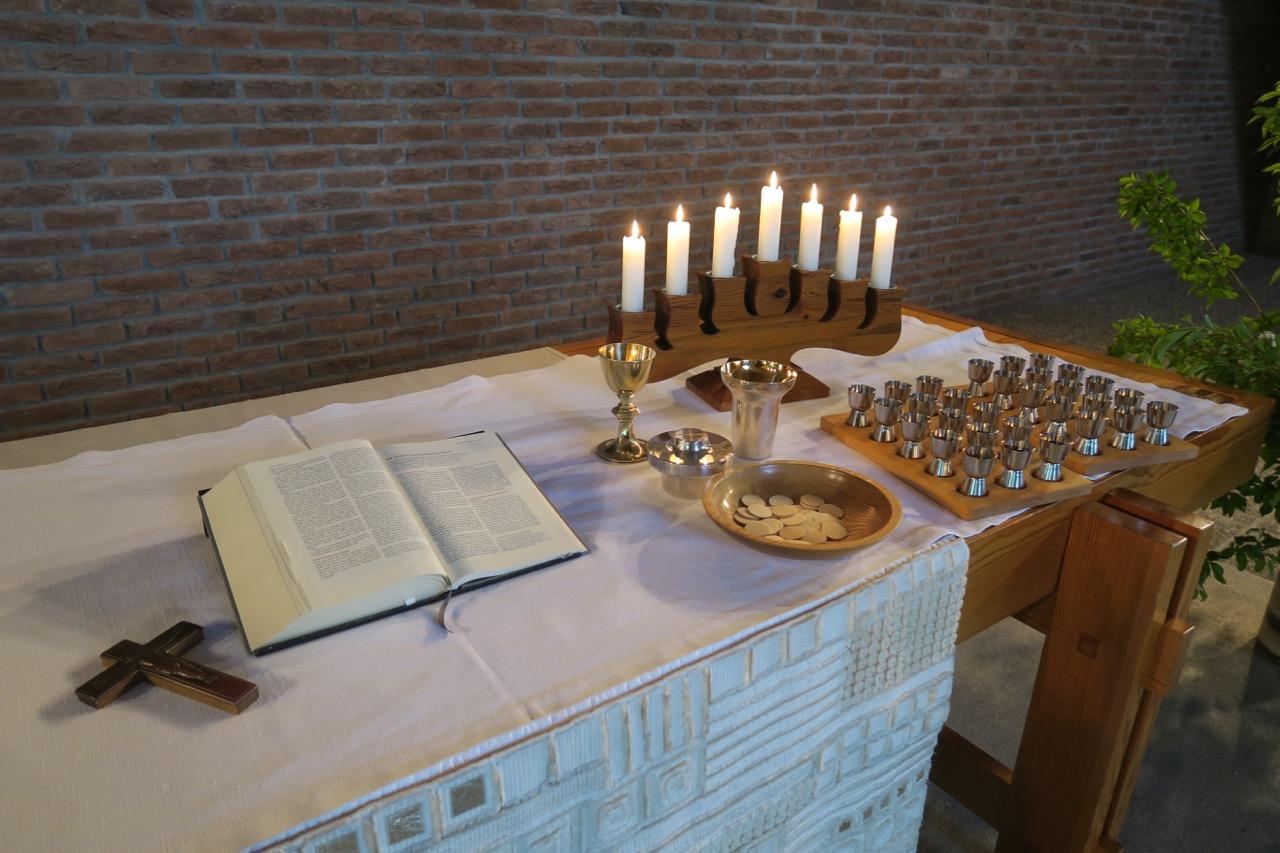 """<a href=""""https://www.visit-a-church.info/glossary#Abendmahlstisch"""" target=""""_blank"""">Altar</a> mit Abendmahlsgerät (Entwurf Heinz Rall, 1967)"""