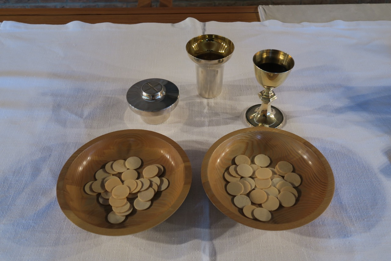 """Brot (<a href=""""https://www.visit-a-church.info/glossary#Hostie"""" target=""""_blank"""">Hostien</a>) und Wein für das Abendmahl"""