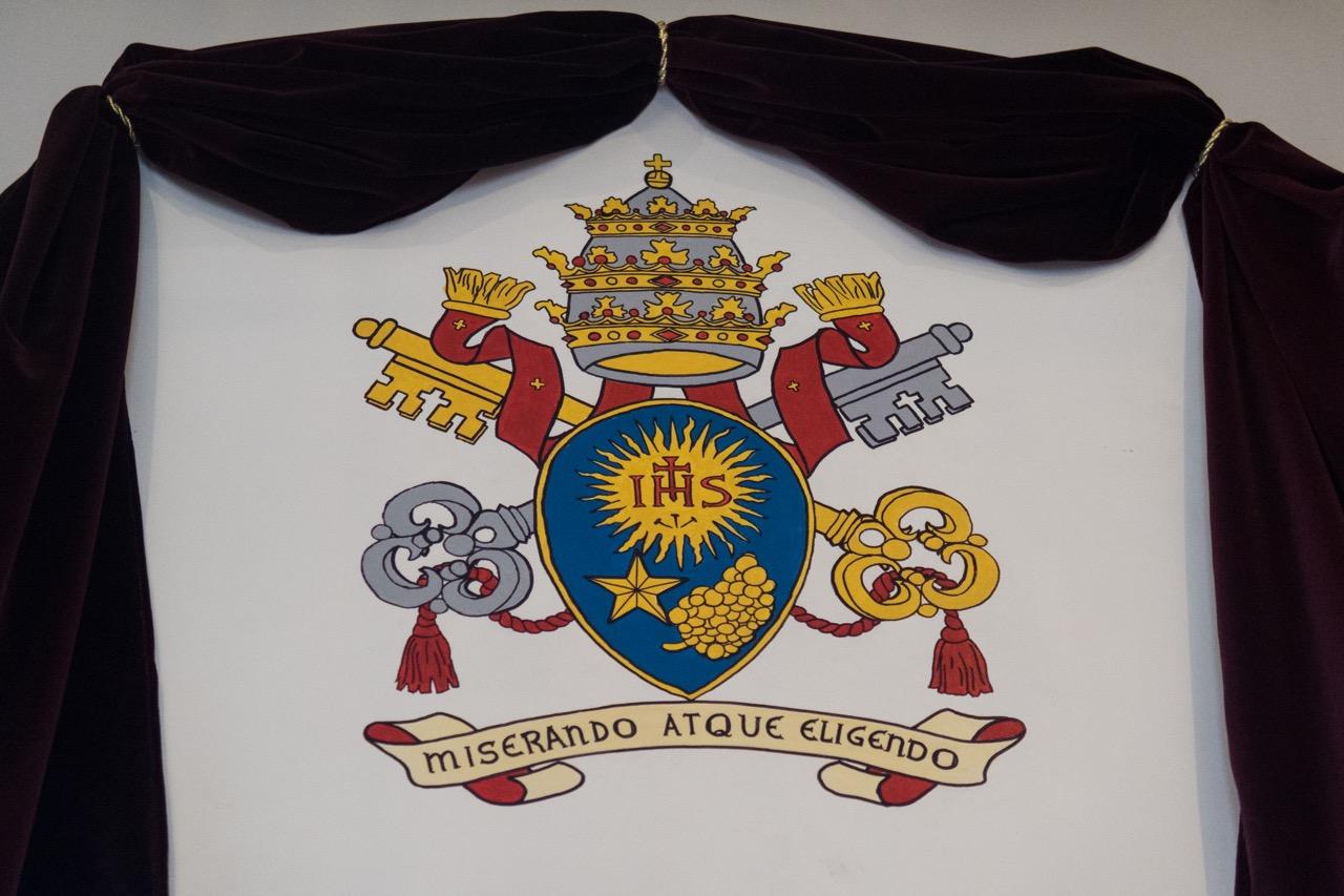 Wappen von Papst Franziskus über dem Portal