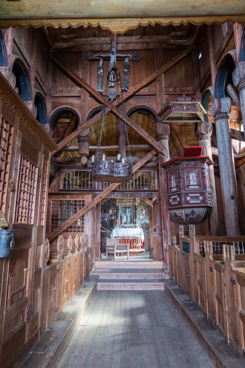 """Innenansicht mit den im Mittelalter eingesetzten Streben, links vorne die Taufstelle """"Funtehuset"""", links hinten der """"Munthe Stuhl"""", beides durch Gitter abgeteilt"""