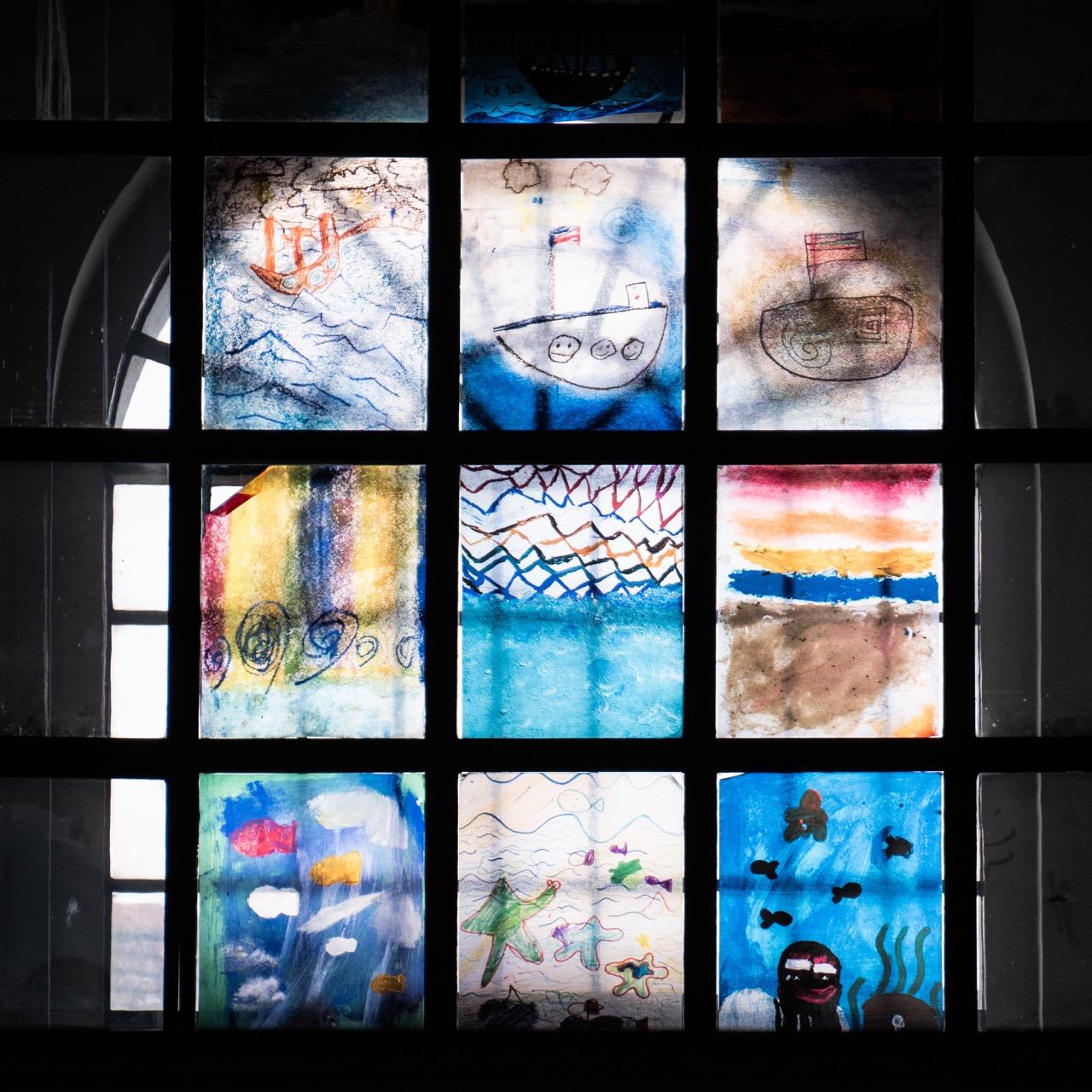 Fenster mit Kinderzeichnungen